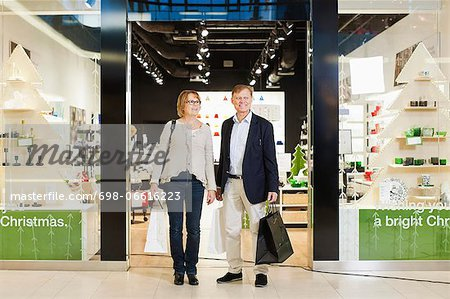 Full length of happy senior couple with shopping bags standing in front of store Stock Photo - Premium Royalty-Free, Image code: 698-06616223