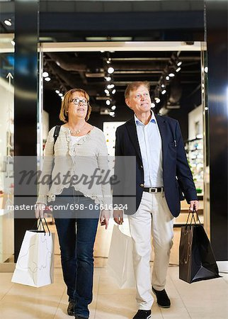 Full length of senior couple with shopping bags walking in mall Stock Photo - Premium Royalty-Free, Image code: 698-06616224