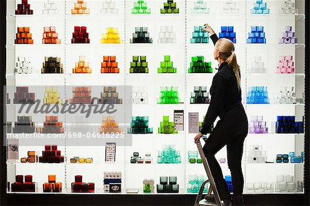 Side view of saleswoman arranging candlestick holders on shelves Stock Photo - Premium Royalty-Free, Image code: 698-06616225