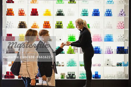 Saleswoman helping senior couple in selecting candlestick holder Stock Photo - Premium Royalty-Free, Image code: 698-06616227