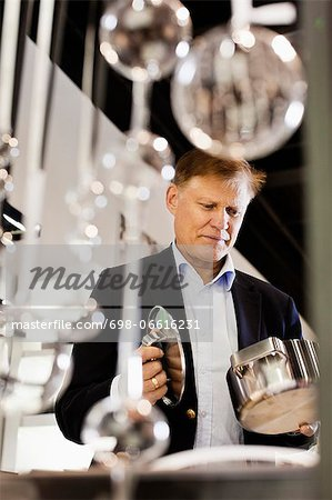 Senior man holding pan and lid in store at shopping mall Stock Photo - Premium Royalty-Free, Image code: 698-06616231