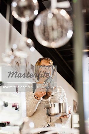 Happy senior woman buying cookware in shopping mall Stock Photo - Premium Royalty-Free, Image code: 698-06616233