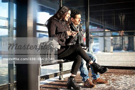Happy friends in warm clothes holding mobile phones while looking away Stock Photo - Premium Royalty-Free, Image code: 698-06616240