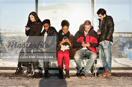 Group of multi ethnic friends using mobile phones on bench Stock Photo - Premium Royalty-Free, Image code: 698-06616244