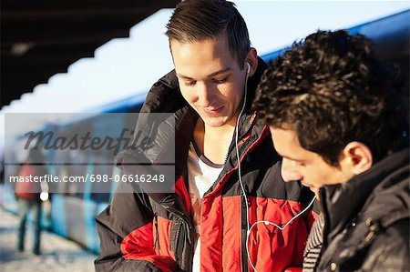 Friends using hands-free device on station Stock Photo - Premium Royalty-Free, Image code: 698-06616248