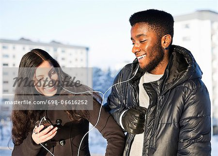 Playful young friends listening music through hands-free device against buildings Stock Photo - Premium Royalty-Free, Image code: 698-06616252