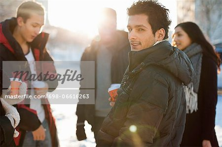 Portrait of young man with friends in warm clothes holding disposable cups Stock Photo - Premium Royalty-Free, Image code: 698-06616263