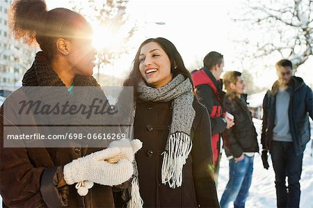 Happy young women in warm clothing with male friends in background Stock Photo - Premium Royalty-Free, Image code: 698-06616269