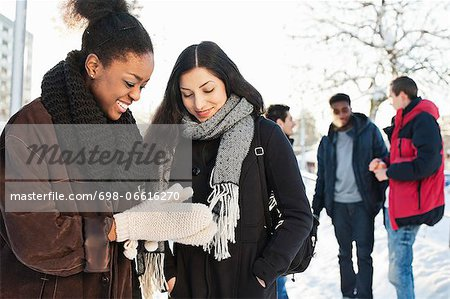 Happy young female friends in warm clothing with men in background Stock Photo - Premium Royalty-Free, Image code: 698-06616270