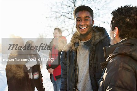 Young men in warm clothing with friends communicating in background Stock Photo - Premium Royalty-Free, Image code: 698-06616271