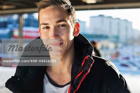 Portrait of young Caucasian man in jacket smiling outdoors Stock Photo - Premium Royalty-Free, Image code: 698-06616283