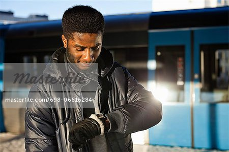 African American young man checking time at railway station Stock Photo - Premium Royalty-Free, Image code: 698-06616284
