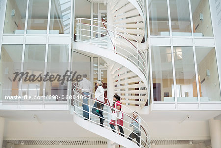 Business people climbing spiral staircase in office Stock Photo - Premium Royalty-Free, Image code: 698-06804003
