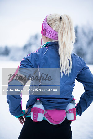 Rear view of woman wearing water bottle belt listening music in winter Stock Photo - Premium Royalty-Free, Image code: 698-06804099