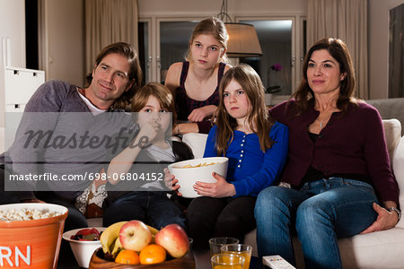 Family of five with bowl of chips watching television in living room Stock Photo - Premium Royalty-Free, Image code: 698-06804152