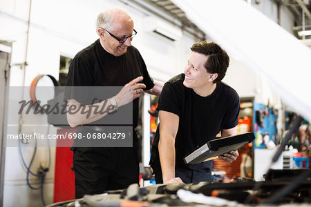 Happy senior male mechanic looking at young coworker at auto repair shop Stock Photo - Premium Royalty-Free, Image code: 698-06804279