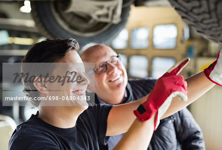 Happy young mechanic explaining tire problems to customer underneath car at auto repair shop Stock Photo - Premium Royalty-Free, Image code: 698-06804343