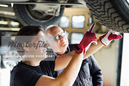 Young mechanic explaining tire problems to customer below car at auto repair shop Stock Photo - Premium Royalty-Free, Image code: 698-06804344