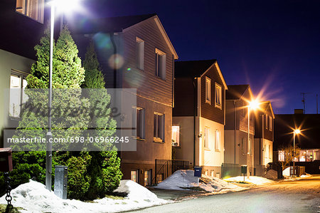 View of houses in a row during winter at night Stock Photo - Premium Royalty-Free, Image code: 698-06966245