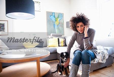 Mature women using mobile phone while sitting with pet dog in living room Stock Photo - Premium Royalty-Free, Image code: 698-06966261