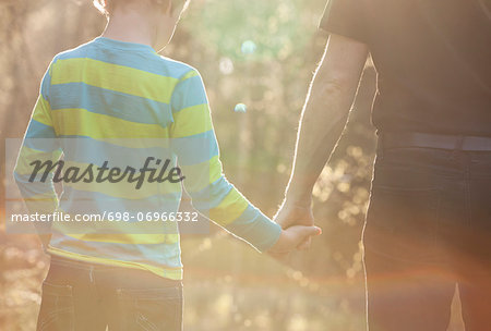 Midsection of boy and father holding hands while standing at park Stock Photo - Premium Royalty-Free, Image code: 698-06966332