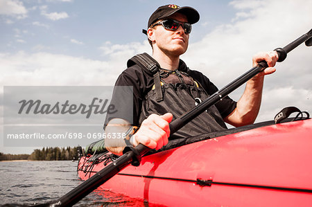 Mid adult man kayaking in lake Stock Photo - Premium Royalty-Free, Image code: 698-06966338