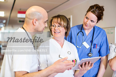 Senior female doctor discussing over digital tablet with colleagues in hospital Stock Photo - Premium Royalty-Free, Image code: 698-06966353