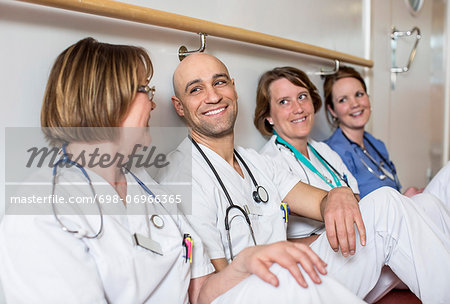 Happy male doctor and female colleagues leaning together on wall in hospital Stock Photo - Premium Royalty-Free, Image code: 698-06966365