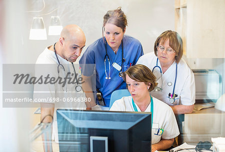 Male and female doctors using computer together in clinic Stock Photo - Premium Royalty-Free, Image code: 698-06966380