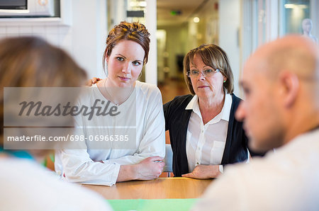 Mother and daughter getting notice from doctors at table in clinic Stock Photo - Premium Royalty-Free, Image code: 698-06966385