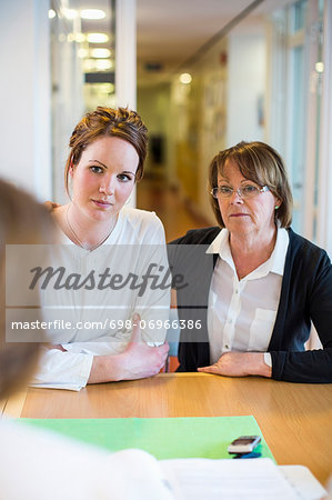 Mother and daughter looking at female doctor at desk in clinic Stock Photo - Premium Royalty-Free, Image code: 698-06966386