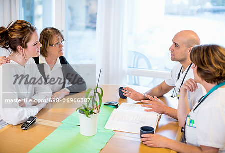 Male and female doctors giving notice to patients at desk in clinic Stock Photo - Premium Royalty-Free, Image code: 698-06966387