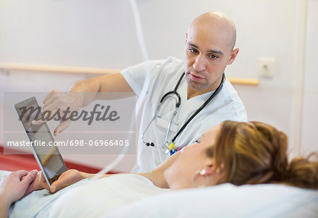 Mid adult male doctor showing digital tablet to patient lying on bed in hospital ward Stock Photo - Premium Royalty-Free, Image code: 698-06966405