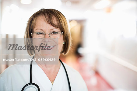Portrait of happy senior female doctor standing in hospital Stock Photo - Premium Royalty-Free, Image code: 698-06966424