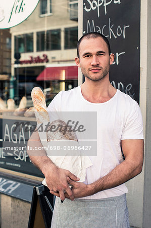 Portrait of male owner holding bread loafs while standing outside bakery Stock Photo - Premium Royalty-Free, Image code: 698-06966427