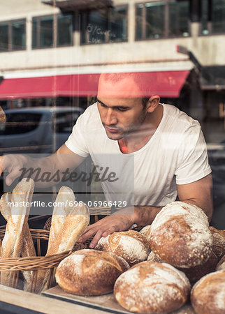 View of male owner working at bakery through display cabinet Stock Photo - Premium Royalty-Free, Image code: 698-06966429