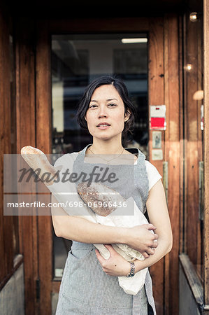 Portrait of confident young female owner holding bread loafs while standing at bakery entrance Stock Photo - Premium Royalty-Free, Image code: 698-06966436