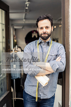 Portrait of confident male fashion designer standing arms crossed at studio doorway Stock Photo - Premium Royalty-Free, Image code: 698-06966440