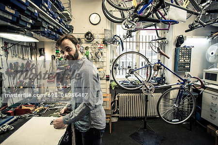 Side view portrait of mid adult repairman working at bicycle repair shop