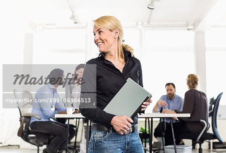 Mature businesswoman looking away while holding laptop with colleagues sitting at desk in background Stock Photo - Premium Royalty-Free, Image code: 698-06966513