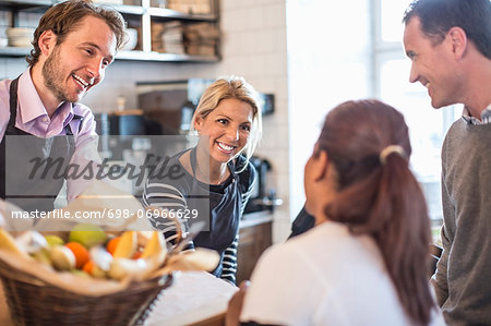 Male and female owner attending customers at counter in restaurant Stock Photo - Premium Royalty-Free, Image code: 698-06966629