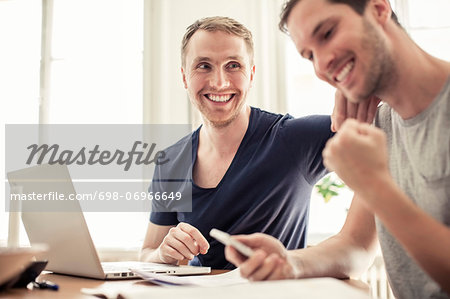 Happy loving homosexual couple with laptop siting at table in home Stock Photo - Premium Royalty-Free, Image code: 698-06966649