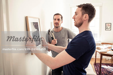 Homosexual couple hanging picture frame on wall at home
