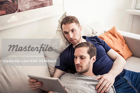 Young homosexual using digital tablet together while relaxing on sofa at home Stock Photo - Premium Royalty-Free, Image code: 698-06966666
