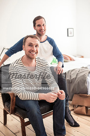 Portrait of happy homosexual couple sitting on chair in bedroom Stock Photo - Premium Royalty-Free, Image code: 698-06966672
