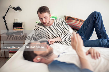 Young gay man reading book with partner listening music on bed at home Stock Photo - Premium Royalty-Free, Image code: 698-06966674