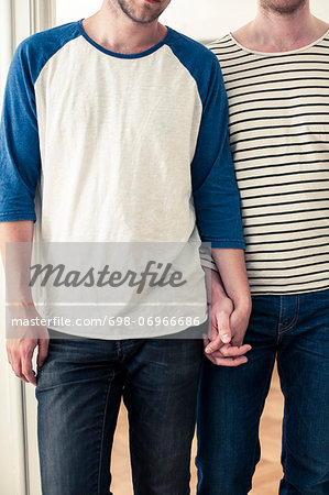 Midsection of young homosexual couple holding hands at home Stock Photo - Premium Royalty-Free, Image code: 698-06966686
