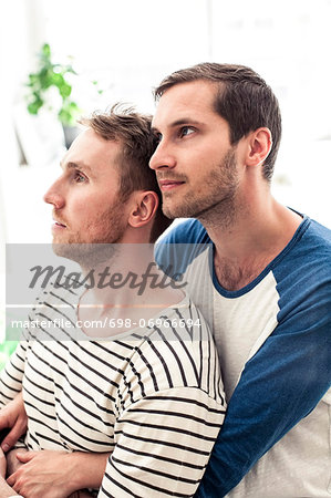 Thoughtful young homosexual couple looking away while embracing at home Stock Photo - Premium Royalty-Free, Image code: 698-06966694