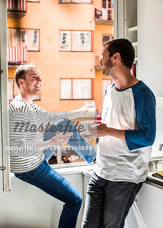 Young homosexual couple having breakfast together by window at home Stock Photo - Premium Royalty-Free, Image code: 698-06966698