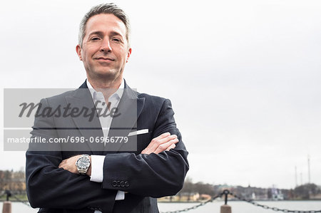 Portrait of mature businessman standing arms crossed against clear sky Stock Photo - Premium Royalty-Free, Image code: 698-06966779